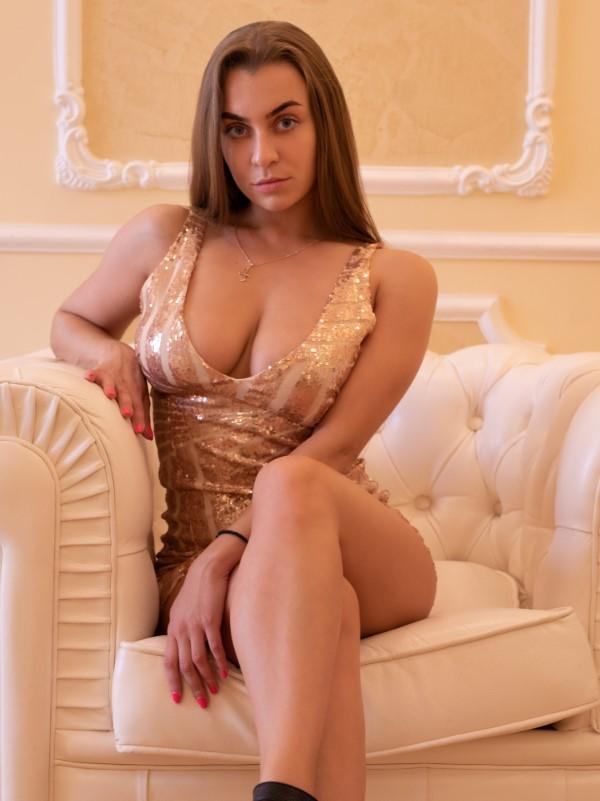 На фотографии роскошная эскорт модель в коротком платье