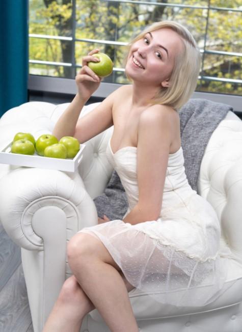 Фотография молодой девушки в белом платье с яблоком в руках
